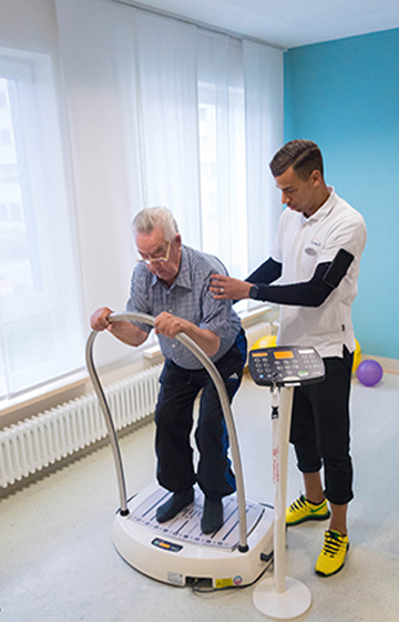 Themenbild: Patient und Trainer bei einer Sportübung