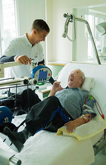 Themenbild: Patient und Trainer bei einer Cardioübung