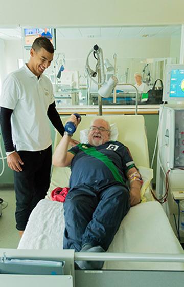 Themenbild: Trainer und Patient bei einer Übung mit Hanteln